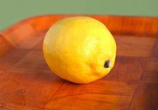 Todavía vida con el limón amarillo maduro en la bandeja marrón Imagen de archivo libre de regalías