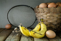 Todavía vida con el plátano, la estafa de bádminton vieja y los huevos en la cesta de bambú Foto de archivo libre de regalías
