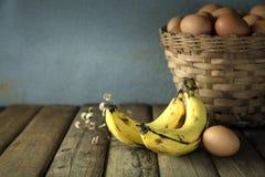 Todavía vida con el plátano y los huevos en la tabla de madera Fotografía de archivo libre de regalías