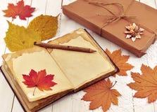 Todavía vida con el presente, el libro abierto de la memoria y las hojas Fotos de archivo libres de regalías