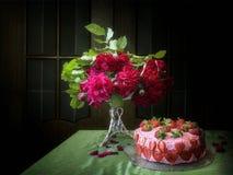 Todavía vida con el ramo de rosas y de torta magentas de la fresa foto de archivo
