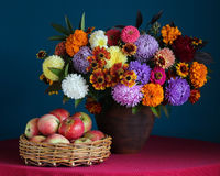 Todavía vida con el ramo del otoño en un jarro y manzanas Foto de archivo
