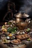 Todavía vida con el samovar, las frutas, el té y la rueda de hilado Imagen de archivo