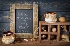 Todavía vida con el tablero, el café y nueces de tiza en un tabl de madera Fotografía de archivo