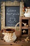 Todavía vida con el tablero, el café y nueces de tiza en un tabl de madera Foto de archivo