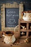 Todavía vida con el tablero, el café y nueces de tiza en un tabl de madera Fotos de archivo