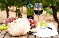 Todavía vida con el vidrio de uvas y de pan de vino rojo en la tabla Fotos de archivo