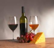 Todavía vida con el vidrio y la botella de vino, de queso y de uvas Imágenes de archivo libres de regalías