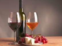 Todavía vida con el vidrio y la botella de vino, de queso y de uvas Imagen de archivo libre de regalías