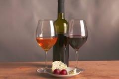 Todavía vida con el vidrio y la botella de vino, de queso y de uvas Fotos de archivo