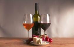 Todavía vida con el vidrio y la botella de vino, de queso y de uvas Imagenes de archivo