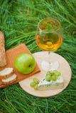 Todavía vida con el vino blanco, el baguette, el queso, la uva y la manzana Imagenes de archivo
