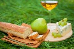 Todavía vida con el vino blanco, el baguette, el queso, la uva y la manzana Fotos de archivo