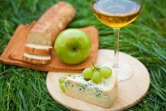 Todavía vida con el vino blanco, el baguette, el queso, la uva y la manzana Foto de archivo