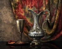 Todavía vida con el vino de jarro, el cubilete del metal y una granada Foto de archivo libre de regalías