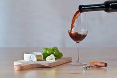 Todavía vida con el vino que es vertido en el vidrio Fotografía de archivo libre de regalías