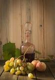 Todavía vida con el vino rojo, las uvas y los melocotones Foto de archivo libre de regalías