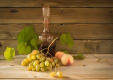 Todavía vida con el vino rojo, las uvas y los melocotones Foto de archivo