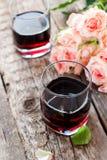 Todavía vida con el vino rojo y el ramo de rosas Fotos de archivo