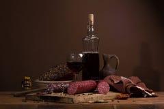 Todavía vida con el vino y la salchicha Imágenes de archivo libres de regalías