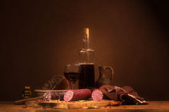 Todavía vida con el vino y la salchicha Imagenes de archivo