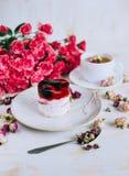 Todavía vida con infusión de hierbas, la torta y las rosas Fotos de archivo libres de regalías