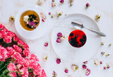 Todavía vida con infusión de hierbas, la torta y las rosas Imagen de archivo libre de regalías