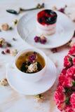 Todavía vida con infusión de hierbas, la torta y las rosas Foto de archivo libre de regalías