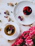 Todavía vida con infusión de hierbas, la torta y las rosas Fotografía de archivo libre de regalías