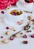 Todavía vida con infusión de hierbas, la torta y las rosas Imagen de archivo