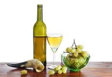 Todavía vida con la botella de vino y de uva aislados sobre blanco Imágenes de archivo libres de regalías