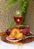 Todavía vida con la botella, el vidrio de vino y los melocotones Foto de archivo libre de regalías