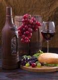 Todavía vida con la botella, el vidrio y las uvas de vino Fotografía de archivo libre de regalías
