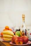 Todavía vida con la botella y las frutas del champán Foto de archivo