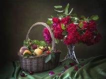 Todavía vida con la cesta de frutas y el ramo de rosas magentas en la tabla fotos de archivo libres de regalías
