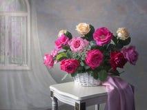Todavía vida con la cesta de rosas multicoloras del jardín en la tabla foto de archivo libre de regalías