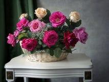 Todavía vida con la cesta de rosas multicoloras del ramo en la tabla imágenes de archivo libres de regalías