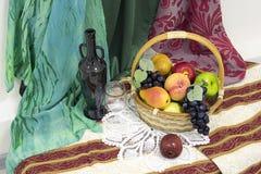 Todavía vida con la cesta, la fruta artificial, la botella vieja y el vidrio Imagenes de archivo