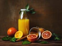 Todavía vida con la fruta y el jugo anaranjados Foto de archivo