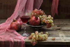 Todavía vida con la granada y el vino rojo Foto de archivo