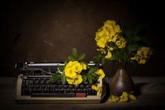 Todavía vida con la máquina de escribir vieja con las flores amarillas en de madera Imágenes de archivo libres de regalías