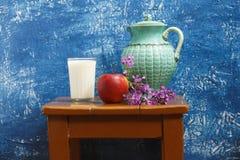 Todavía vida con la manzana, la leche y flores Foto de archivo libre de regalías