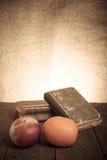 Todavía vida con la manzana, la naranja y una pila de libros viejos en el wo viejo Imagen de archivo libre de regalías