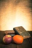 Todavía vida con la manzana, la naranja y una pila de libros viejos en el wo viejo Fotos de archivo libres de regalías