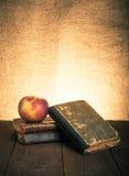 Todavía vida con la manzana y una pila de libros viejos en vieja etiqueta de madera Imágenes de archivo libres de regalías