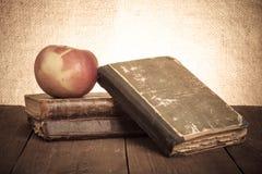 Todavía vida con la manzana y una pila de libros viejos en vieja etiqueta de madera Imagenes de archivo