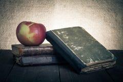 Todavía vida con la manzana y una pila de libros viejos en vieja etiqueta de madera Imagen de archivo libre de regalías