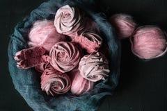 Todavía vida con la melcocha de la baya con los ovillos rosados en fondo oscuro Foto de archivo