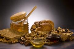Todavía vida con la miel, tuercas, pan, bollo. Fotografía de archivo
