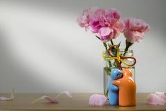 Todavía vida con la muñeca y la flor de cerámica en la tabla de madera sobre gru Foto de archivo